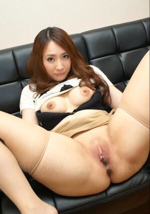 Breathtaking Japanese broad with red hair exposes on leather couch her assets